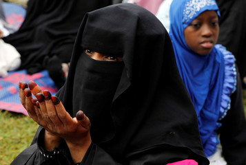 A Muslim woman participates in Eid al-Fitr prayers to mark the end of the holy fasting month of Ramadan at the Sir Ali Muslim Club Ground in Nairobi, Kenya