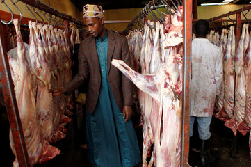 A Muslim man shops for goat meat inside a slaughterhouse after Eid al-Fitr prayers to mark the end of the holy fasting month of Ramadan in Nairobi
