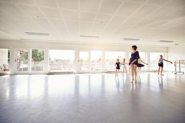 Woman teaching girls ballet group in class