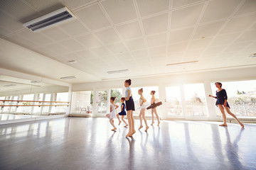 Little female ballet performers exercising in class