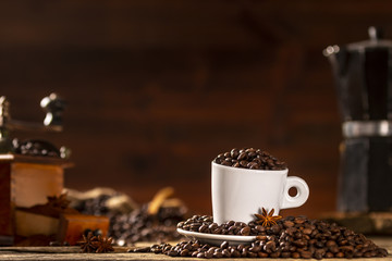 White cup covered coffee beans with various accesories