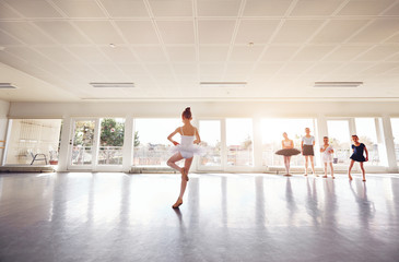 Little girl dancing ballet and group watching in class