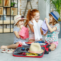 Three little girls packed their clothes in a suitcase. Square. Concept, lifestyle, childhood, trip, vacation, family tourism