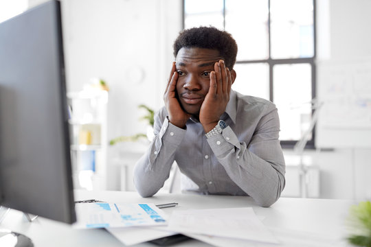 business, people, deadline and technology concept - stressed african american businessman with computer and papers at office