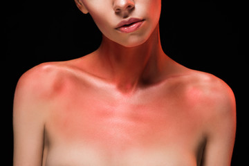cropped view of nude woman with red body art, isolated on black