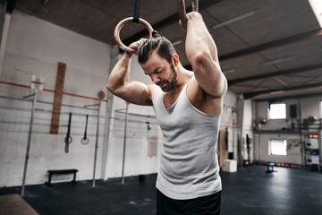 Fit young man taking looking tired after exercising on rings