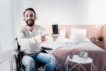 My new gadget. Content disabled man sitting in a wheel chair and listening to music