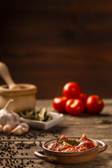 Meat and tomato meal with fresh vegetables and ingredients on dark background