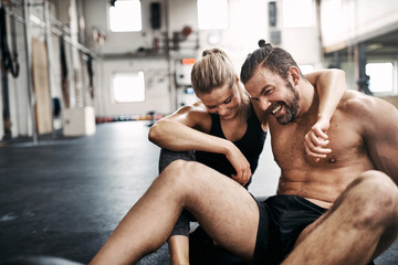 Affectionate couple sitting together on the floor of a gym