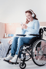 My leisure. Cheerful disabled woman sitting in a wheel chair and listening to music