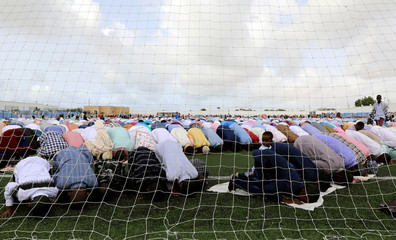 Muslim faithful attend Eid al-Fitr prayers to mark the end of the holy fasting month of Ramadan behind a goal post inside the soccer stadium in Hodan district of Mogadishu