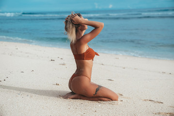 A young slender girl with an even tan in a long orange open swimsuit resting on a deserted beach with white sand. The concept of relaxation, harmony, relaxation.