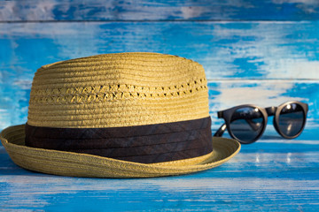 straw hat and glasses on wooden blue background