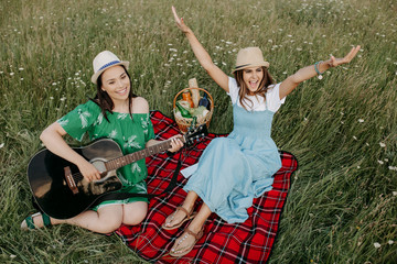 Two attractive young women sitting down on the picnic blanket and have fun. Music and freedom concept.