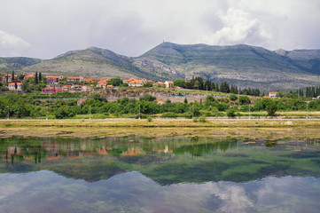 Landscape with hills, mountains and small town on river bank is reflected in water. Bosnia and Herzegovina, view of Trebisnjica river near Trebinje city