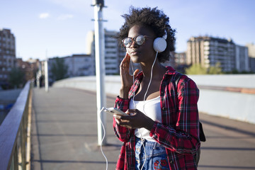 Portrait of young woman on a bridge listening music with headphones