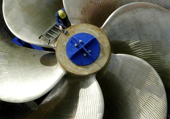 A worker climbs up a huge marine propeller screw in Hamburg.