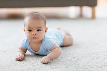 babyhood, childhood and people concept - sweet little asian baby boy lying on floor