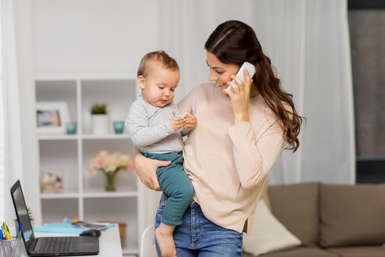 motherhood, multi-tasking, family and technology concept - happy mother with baby calling on smartphone at home
