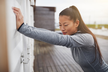 Young Asian woman stretching against a wall before jogging