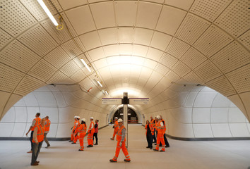 Crossrail employees walk in the new Farringdon underground station of the Elizabeth line which opens in December 2018, in London
