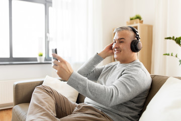 technology, people and lifestyle concept - happy man with smartphone and headphones listening to music at home