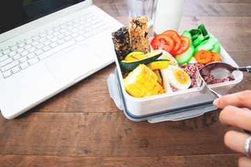 Healthy lunch box with rice berry, boiled eggs, carrot, tomatoes, corns, pumpkin and cereal bars on workspace desk, Food and Health