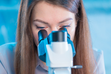 Girl student with microscope in the laboratory
