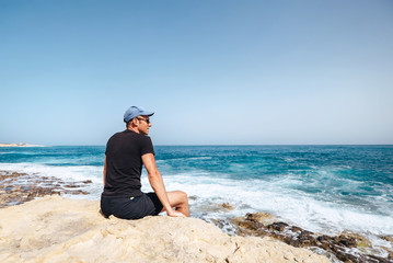 Man sits on rocky cliff near the seaside and looks on waves