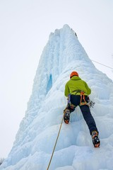 Alpinist man with  ice tools axe in orange helmet climbing a large wall of ice. Outdoor Sports Portrait