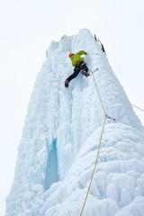 Alpinist man with  ice tools axe in orange helmet climbing