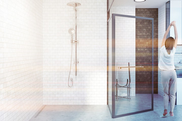 White brick bathroom with glass door, woman