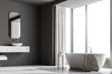 Gray bathroom interior, white bathtub and sink