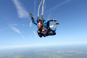 Skydiving. Two men are flying in the blue sky.
