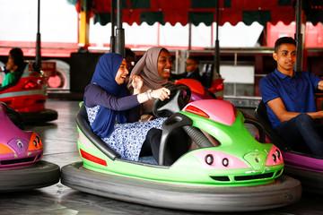 People enjoy fairground attractions following Eid al-Fitr prayers, in Small Heath Park in Birmingham