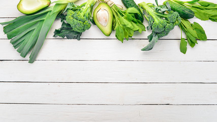 Green vegetables and fruits. On a white wooden background. Healthy food. Top view. Copy space.