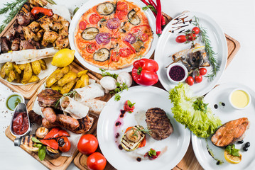 Big set of different dishes with meat, vegetables, pizza and spices flatlay on white background