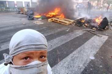 A VENEZUELAN OPPOSITION PROTESTER LOOKS ON DURING RIOTS IN CARACAS.