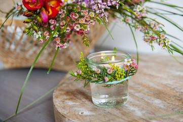 Tischdekoration mit Gräsern und feinen Feldblumen und bluten und teelicht