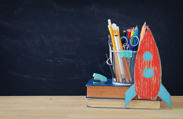 Back to school concept. rocket and pencils over open book in front of classroom blackboard.