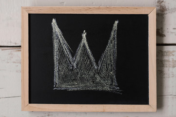 A crown drawn on small blackboard. Wealth and authority symbol