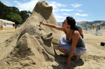 "An artist works on a sand sculpture during the Sand Sculpture Festival dedicated to the movie ""Madagaskar"" at Rajska (Paradise) beach in Lopar"