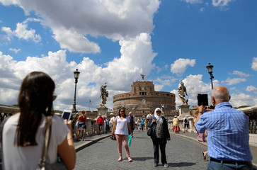 Tourists pose for a picture in front of Castel Sant'Angelo in Rome