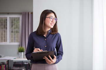 Happy beautiful business woman with clipboard in the office. Copy space Wall mural
