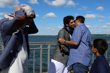 Muslim men greet each other after Eid Al-Fitr morning prayers at Bensonhurst Park in the Brooklyn, New York