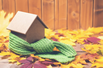 Green scarf around a miniature house on autumn leaves background. Concept of protecting or isolating house.
