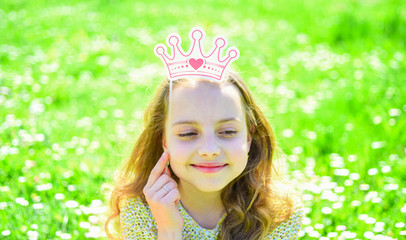 Girl sits on grass at grassplot, green background. Girl on dreamy face spend leisure outdoors. Child posing with cardboard crown for photo session at meadow. Princess concept.
