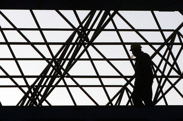 A Chinese worker is silhouetted amidst metal pipes at Shougang Group steel factory on the outskirts ...