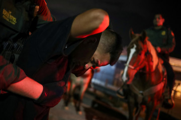 Border Patrol agents on horses apprehend a man who illegally crossed into the U.S. from Mexico in Sunland Park, New Mexico