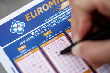 A woman fills out a grid of a lottery ticket for Euro Millions, a lottery game draw, by the French national lottery company Francaise des Jeux (FDJ) in this picture illustration